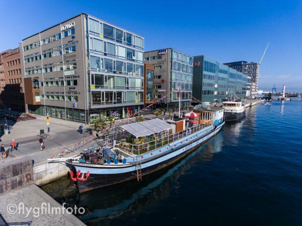 Vid Anna Lindhs plats i Malmö hamn ligger vackra teaterfartyget Blå Båten (och systerfartyget Tintin). Här finns också en rad kontor, bland annat för Länsförsäkringar, KPMG, Acando, Celemi och Centric. Bakom sträcker gröna Orkanen ut sig, Malmö Högskolas byggnad med bibliotek. Flygfoto: @2016 Marko T Wramén/Flygfilmfoto